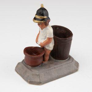 Antique terracota peeing boy figure , firemen helmet, match holder