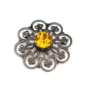 Vintage metal brooch with a yellow stone
